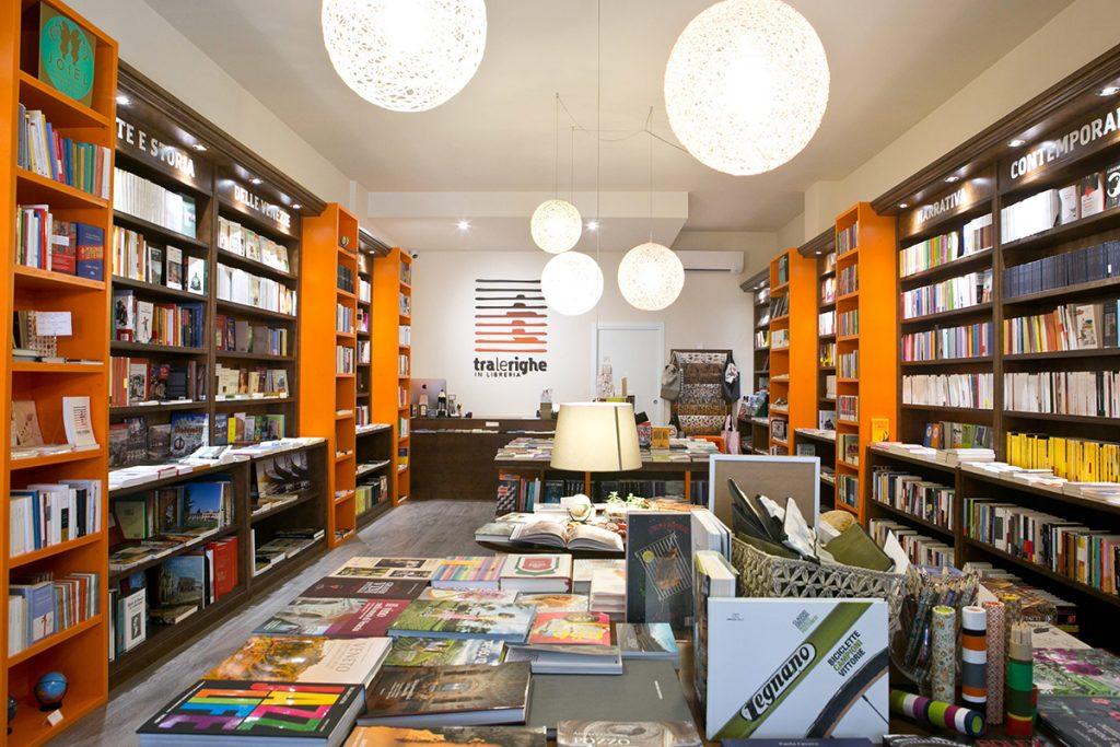 Librerie Indipendenti_interno libreria con scaffali di libri e tavoli con libri e lampadari sferici