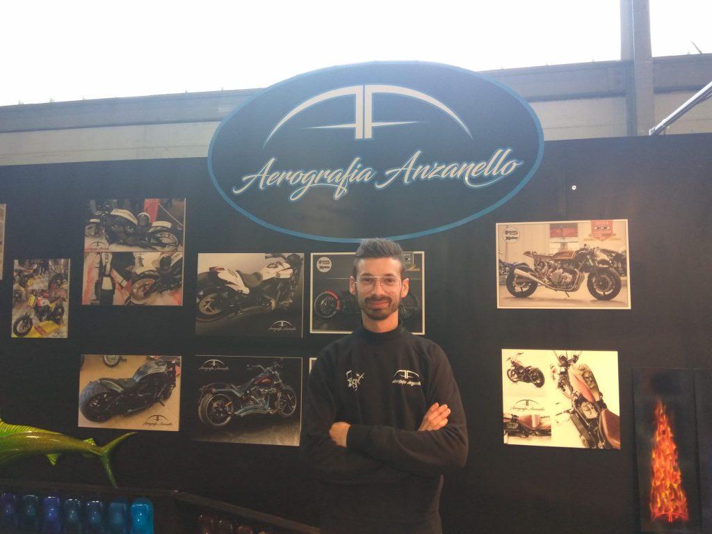 Davide Anzanello con le foto dei suoi lavori sullo sfondo