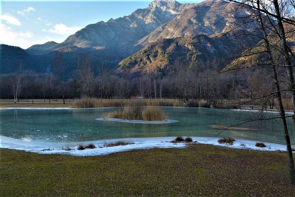 Vista invernale delle sponde del lago di Cavazzo coperte di neve fresca