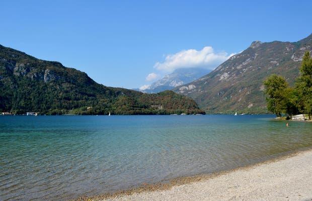 Vista delle acqua trasparenti del lago e della spiaggia di ciottoli che lo circonda