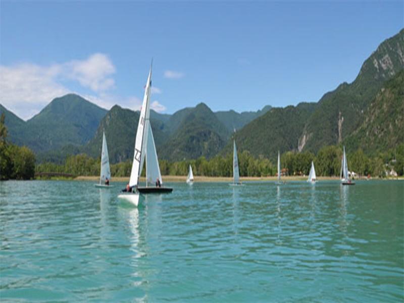 Barche a vela che solcano la superficie del lago di Cavazzo