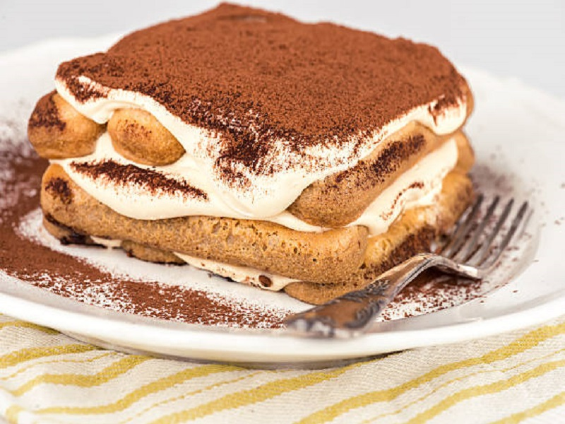 Tiramisu Cake In A White Plate With A Fork
