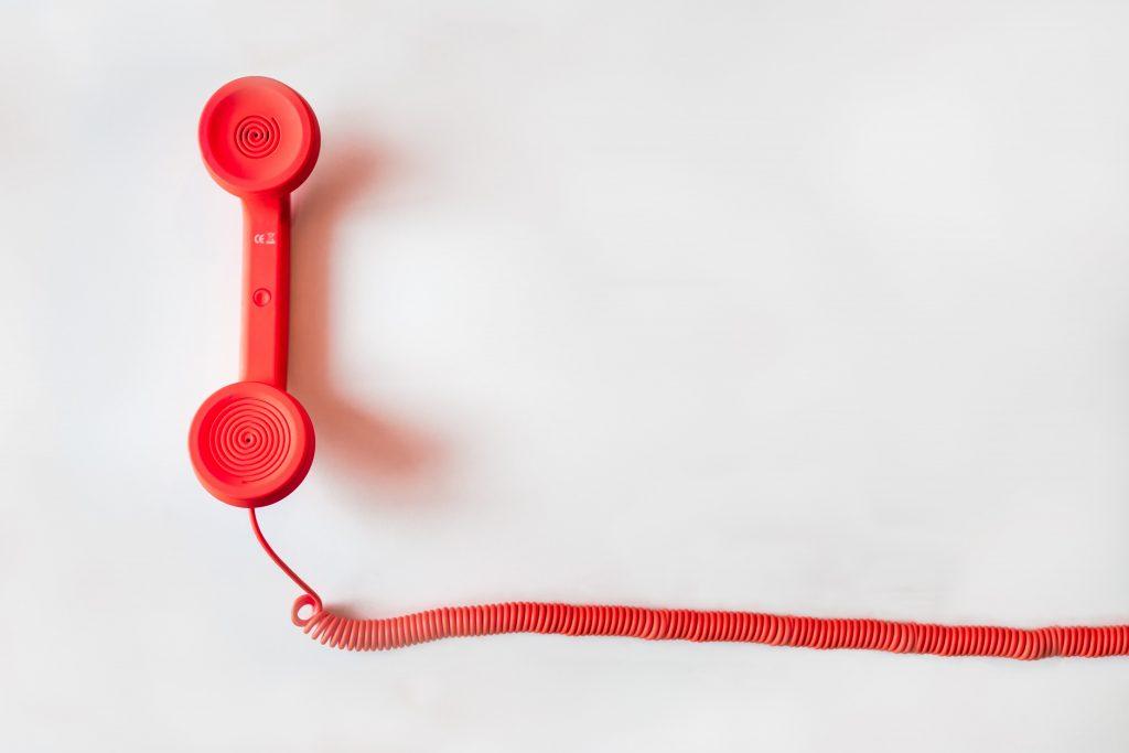 la cornetta di un telefono rosso con un lungo filo