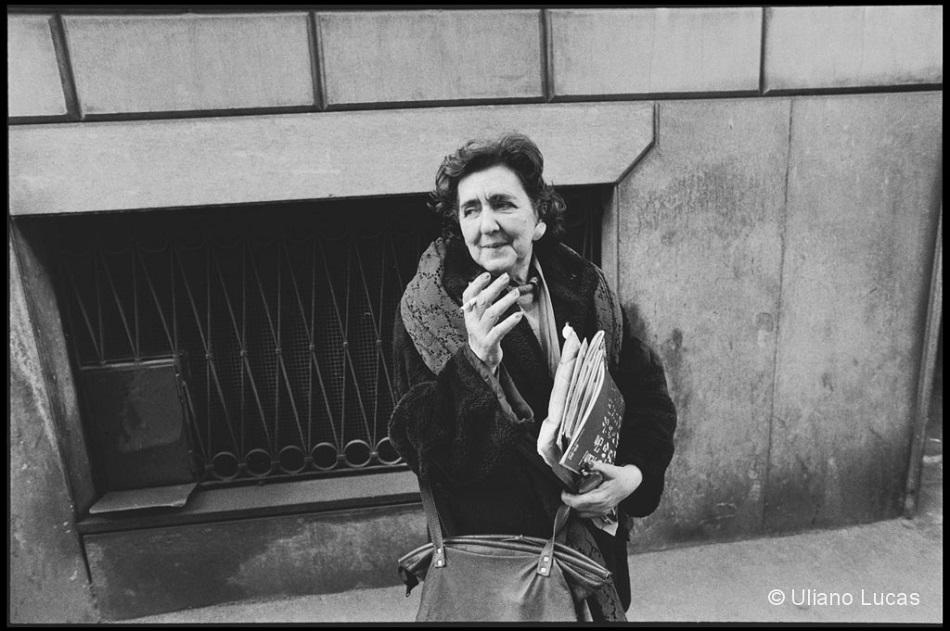 foto in bianco e nero di Alda Merini che fuma una sigaretta in mezzo alla strada