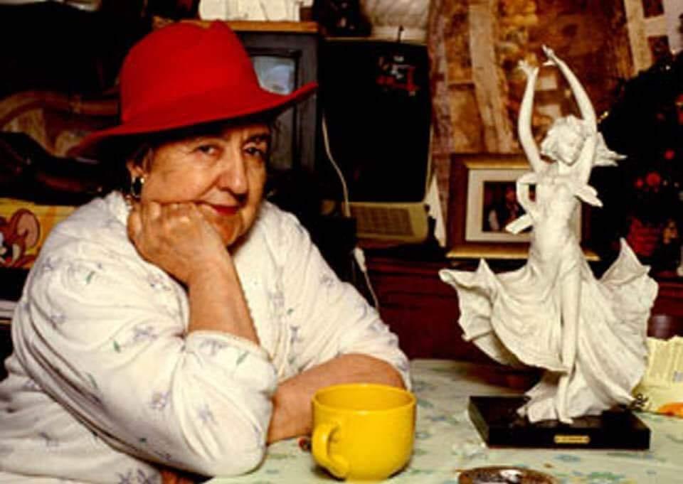 Alda Merini seduta al tavolo con un cappello rosso e un tazzone del caffè giallo
