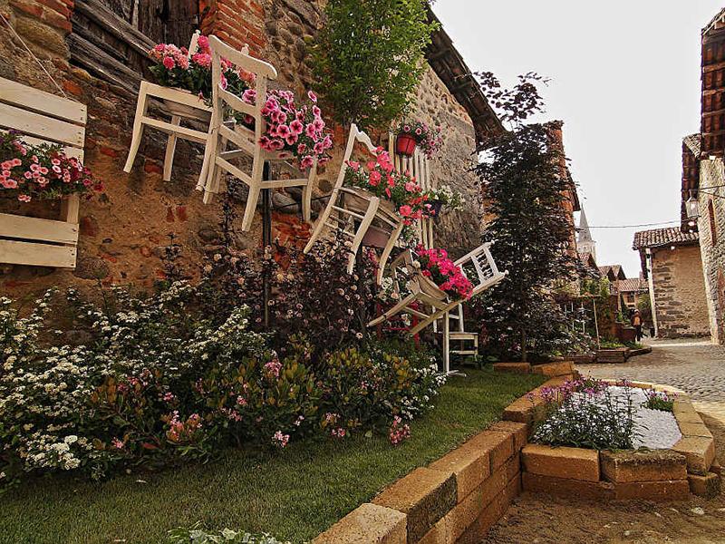 """Candelo in Fiore, parete esterna di una casa """"abbellita"""" con sedie di legno e fiori sulle sedute"""