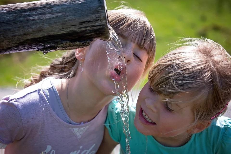 Acqua Equa Bambini Che Bevono ad una sorgente