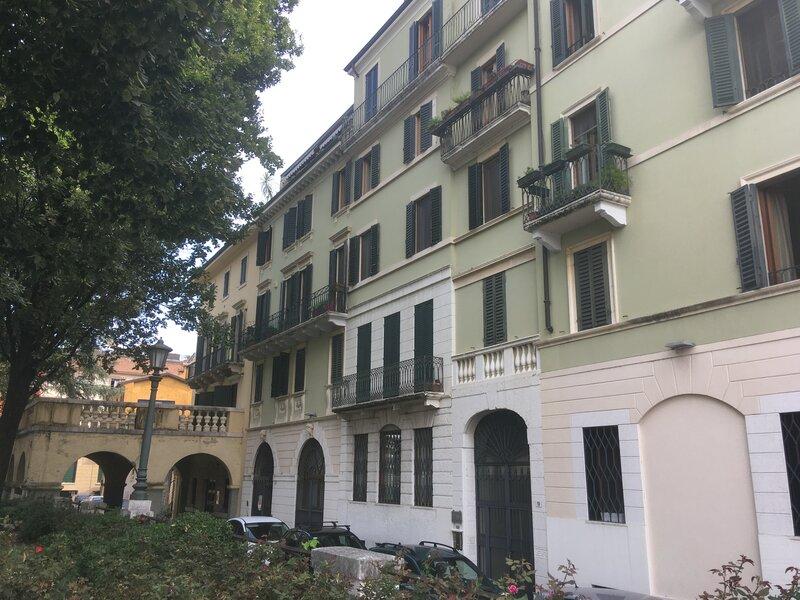 Riva San Lorenzo .Facciata laterale verde e bianca con  inferriate e balconi dove sono attaccati dei vasi di fiori