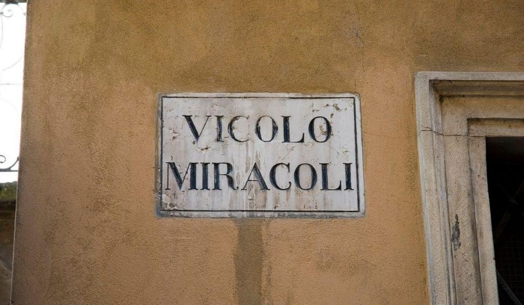 """Un muro giallo con sopra l'Insegna della via """"Vicolo Miracoli"""""""