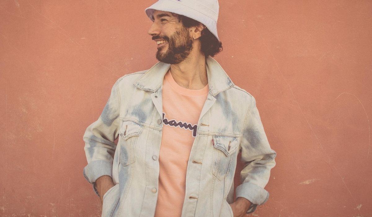 Mosè Santamaria di Profilo: abiti primaverili e sfondo arancione che dà colore alla foto.